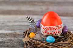Red Easter egg decorated with lace in small nest on wooden background Stock Photos
