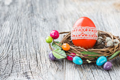 Red Easter egg decorated with lace in small nest on wooden background. Selective focus Stock Photo