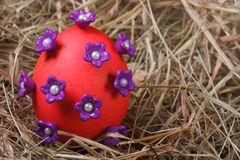 Red easter egg decorated with purple flowers Royalty Free Stock Image