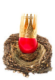 Red easter egg with golden crown decoration. In wooden nest isolated on white background Royalty Free Stock Images