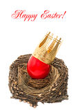 Red easter egg with golden crown decoration. In wooden nest isolated on white background with sample text Happy Easter Royalty Free Stock Photos