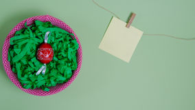 Red easter egg in a nest. Easter egg in front of green background with a card for free text Stock Photo