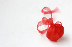 Red easter egg with ribbon, on white surface Royalty Free Stock Images