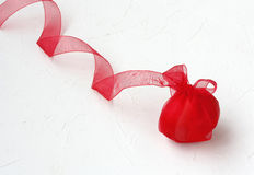 Red easter egg with ribbon, on white textured surface Royalty Free Stock Photo