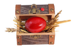 Red Easter egg in the treasure box. Isolated on white Royalty Free Stock Image