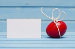 Red Easter egg with white bow on blue wooden background with blank card Royalty Free Stock Images