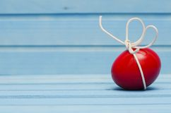 Red Easter egg with white bow on blue wooden background Royalty Free Stock Photo