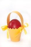 Red easter egg in yellow carton basket Stock Photos