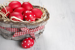 Red Easter eggs in basket Royalty Free Stock Image