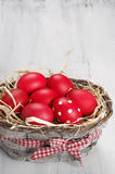 Red Easter eggs in basket. Traditional red and dotted Easter eggs in gray basket on rustic wood background Royalty Free Stock Images