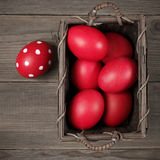 Red Easter eggs in basket Stock Photography