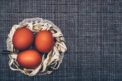 Red Easter Eggs in a decorative nest on a brown background stock photo