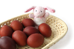 Red Easter eggs and the hare in a wicker tray Royalty Free Stock Photos