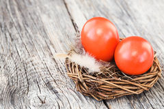 Red Easter eggs in little nest on old wooden table. Selective focus Stock Photo