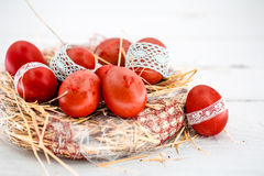 Red Easter eggs in a nest of hay Stock Photo