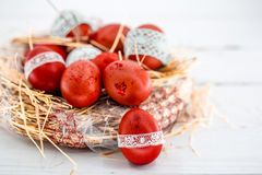 Red Easter eggs in a nest of hay Royalty Free Stock Images