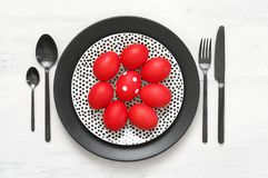 Red Easter eggs in plate with silverware stock images