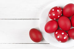 Red Easter eggs in plate. Traditional red and dotted Easter eggs in white plate on white wood background. Top view point Stock Image