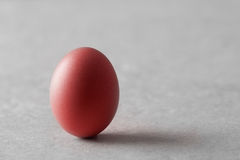 Red Egg. A single red dyed egg standing on end on a grey marble table Stock Photo