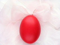 Red Egg and Pink Bow. An egg dyed red for Easter and a pink bow Royalty Free Stock Photography