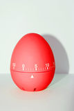 Red egg timer in front of white background Stock Images