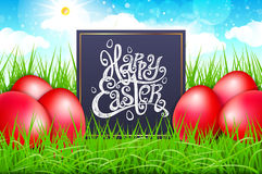 Red eggs in a field of grass with blue sky. happy easter lettering modern calligraphy, vector. Art Royalty Free Stock Photos
