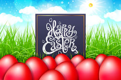 Red eggs in a field of grass with blue sky. happy easter lettering modern calligraphy, vector Royalty Free Stock Photos