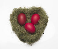 Red eggs in a nest on a white background. Three red eggs in a nest in the form of heart on a white background Royalty Free Stock Image
