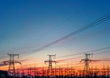 Red eléctrica de alto voltaje, en la puesta del sol foto de archivo libre de regalías