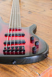 Red electric bass guitar. Lying on table Royalty Free Stock Photos