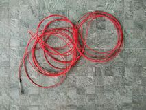 Red electric cord. On grey tile floor background royalty free stock image