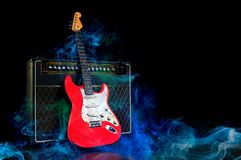 Red electric guitar and amplifier surrounded by smoke stock images