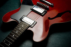 Red electric guitar on back. Red electric guitar laying on back on dark surface Stock Photos