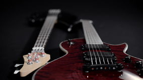 Red electric guitar and black bass, lie side by side.