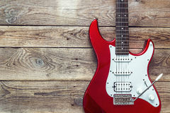 Red electric guitar on grunge wooden planks background. Place for text. Top view stock photos