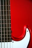 Red Electric Guitar Isolated Red Bk. A red electric guitar isolated against a red background in the vertical format Royalty Free Stock Photos