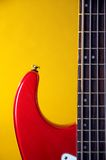 Red Electric Guitar Isolated On Yellow. A red electric guitar isolated against a yellow background in the vertical format Stock Image