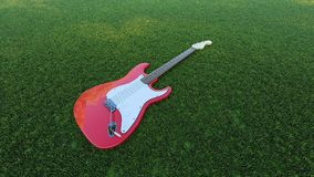 A red guitar in the grass field stock photos