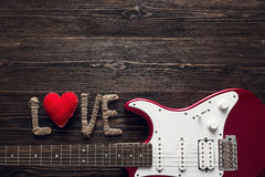 Red electric guitar with the word love and heart on a dark woode Stock Image