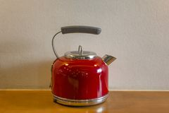 Red electric kettle with a gray handle close-up stands on a yellow wooden surface of the table against the background of a white royalty free stock images