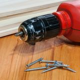 An electric screwdriver and some screws on a wooden table. A red electric screwdriver and some screws on a wooden table. Square composition Royalty Free Stock Photography