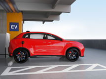 Red electric SUV recharging in parking garage Royalty Free Stock Images