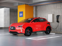 Red electric SUV recharging in parking garage Royalty Free Stock Photography