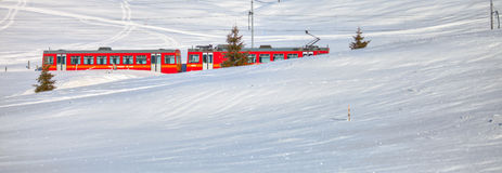 Red Electric Train. Electric powered commuter train travelling thorugh a snow covered landscape in rural Switzerland Stock Photography