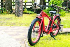 Red electrobicycle standing on a green grass in rainy day royalty free stock image