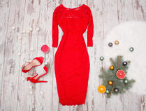 Red elegant lace dress, red shoes on a wooden background, fir branch with ornaments and citrus. Stock Photos