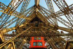 Red elevator brings tourists down the shaft in the metal Eiffel tower structure in Paris. Stock Photos