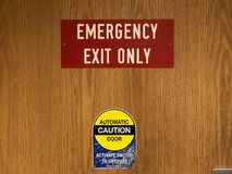 Red emergency exit and automatic door caution sign on clinic doo stock photos