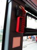 Red emergency hammer for break glass windows. Hammer hangs on the wall near the window in the bus Royalty Free Stock Image