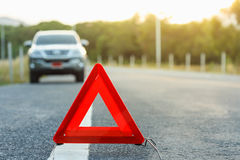 Red emergency stop sign and broken silver car on the road Stock Photos